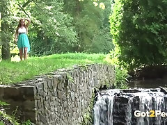 Sexy babe pees near a waterfall